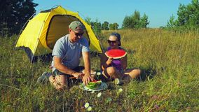 愉快的男人和妇女在一个帐篷附近在森林A人切一个西瓜与一把刀子在大大块 影视素材
