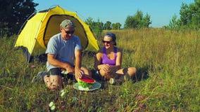 愉快的男人和妇女在一个帐篷附近在森林A人切一个西瓜与一把刀子在大大块 股票录像