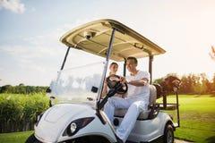 愉快的男人和妇女在一辆白色高尔夫车坐,在高尔夫俱乐部的路站立 免版税库存图片