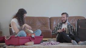 愉快的男人和妇女在地板上在家在皮革沙发前面,包装手提箱在旅行前 妻子投掷 股票录像