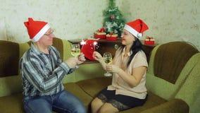 愉快的男人和妇女在家庆祝圣诞节与杯香槟和孟加拉蜡烛 股票录像