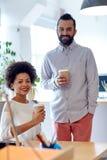 愉快的男人和妇女饮用的咖啡在办公室 免版税库存照片