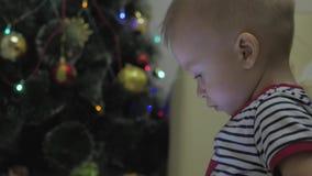 愉快的男婴戏剧和神色在片剂在圣诞树附近在内部家 夜Xmas 股票录像