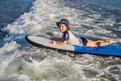 愉快的男婴-在冲浪板的年轻冲浪者乘驾有在海的乐趣的 库存图片