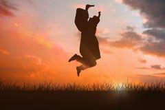 愉快的男学生的综合图象毕业生长袍跳跃的 库存图片