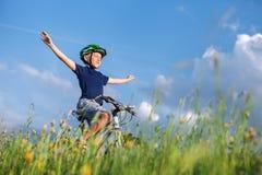 愉快的男孩乘驾没有手的一辆自行车和享用与阳光 图库摄影