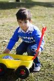 愉快的男孩他的西班牙使用的玩具卡&# 免版税库存图片