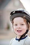 愉快的男孩佩带的自行车盔甲 免版税库存照片