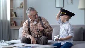愉快的男孩使用与玩具飞机的,祖父前飞行员感到骄傲为孙子 免版税库存照片