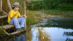 愉快的男孩去钓鱼在河,有a的一位儿童渔夫 免版税图库摄影