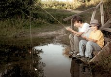 愉快的男孩去钓鱼在河,渔夫的两个孩子有一根钓鱼竿的在湖岸  库存照片