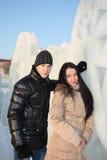 年轻愉快的男孩和女孩在冬天站立近的冰墙壁 免版税库存图片