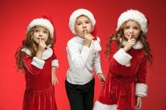 愉快的男孩和女孩在圣诞老人帽子有礼物盒的在演播室 免版税图库摄影