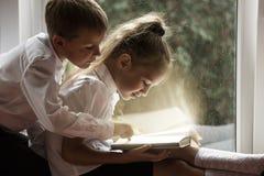 愉快的男孩和女孩坐在Th的窗台阅读书 库存图片