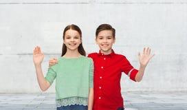 愉快的男孩和女孩挥动的手 库存图片