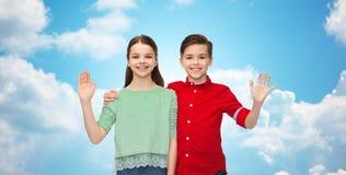 愉快的男孩和女孩挥动的手 免版税库存照片