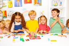愉快的男孩和女孩有彩色塑泥的在教室 免版税图库摄影