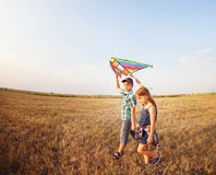 愉快的男孩和小女孩有明亮的风筝的在草甸 免版税图库摄影