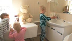 愉快的男孩在卫生间里洗他的有肥皂的手并且刷他的牙 孩子爱水和卫生学做法 水活动性 股票录像