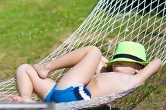 愉快的男孩在吊床睡觉 在帽子的焦点 免版税库存图片