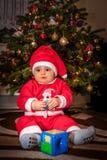 愉快的男孩在圣诞树下 免版税库存图片