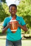 愉快的男孩在有橄榄球的公园 免版税库存图片