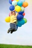 愉快的男孩在有colorfull气球的草甸跳 免版税库存图片