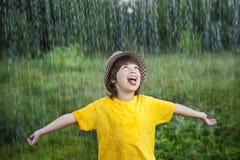 愉快的男孩在雨夏天户外 免版税库存图片