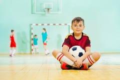 愉快的男孩坐与足球的地板 免版税库存图片