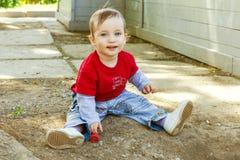 愉快的男孩坐潮湿的地面 免版税库存照片