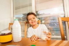 愉快的男孩对负玻璃用坐在桌上的牛奶 库存照片