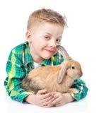 愉快的男孩拥抱兔子 背景查出的白色 图库摄影