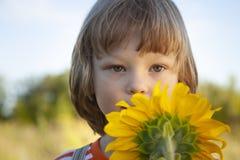 愉快的男孩用向日葵户外 儿童游戏在庭院里 库存图片