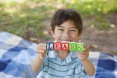 愉快的男孩藏品块字母表'在公园学会' 免版税库存照片