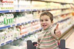 愉快的男孩4年在架子背景的一个超级市场用牛奶和酸奶 太阳光芒 库存图片