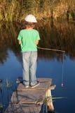 愉快的男孩去钓鱼在河,有a的一位儿童渔夫 图库摄影