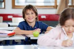愉快的男小学生图画画象在教室的 免版税库存照片