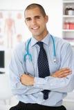 愉快的男性医生在诊疗室坐了 免版税库存照片