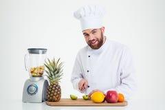愉快的男性厨师切口果子的画象 免版税库存图片