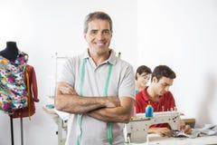 愉快的男性在缝合的工厂横渡的裁缝常设胳膊 免版税库存图片