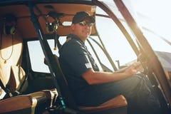 愉快的男性飞行员在直升机驾驶舱内 库存照片