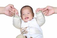 愉快的男婴在白色背景中的握父母手指 免版税库存照片