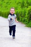 愉快的男婴,跑春天街道 免版税库存照片