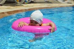 愉快的白白种人儿童女婴小孩画象室外的游泳池的 漂浮的学龄前男孩训练与 库存图片
