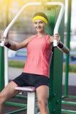 愉快的白种人亭亭玉立的女运动员画象有专业的成套装备的举重锻炼 库存照片
