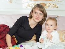 愉快的白种人家庭母亲和女儿在床上在家 免版税库存照片