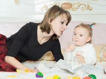 愉快的白种人家庭母亲和女儿在床上在家 免版税库存图片