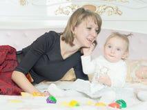 愉快的白种人家庭母亲和女儿在床上在家 图库摄影