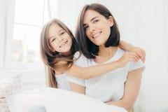 愉快的白种人母亲画象有迷人的微笑和她的小女儿的拥抱与爱妈咪,在心情,摆在  免版税库存照片