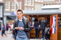 愉快的白种人游人用与葱和netherland旗子的新鲜的鲱鱼在阿姆斯特丹 室外传统荷兰的食物 免版税库存照片